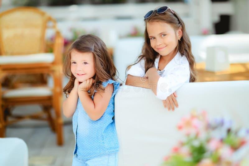 Twee leuke meisjes die zich in verbindingsdraden en zonglazen bevinden op de terrasachtergrond in de studio De zomer, pret, famil stock afbeeldingen