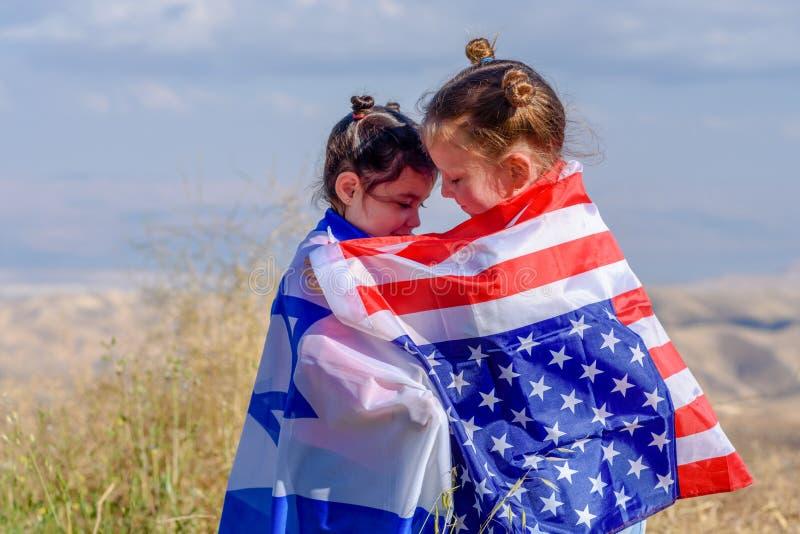 Twee leuke meisjes met Amerikaanse en Israëlische vlaggen Twee naties één hartconcept royalty-vrije stock afbeelding