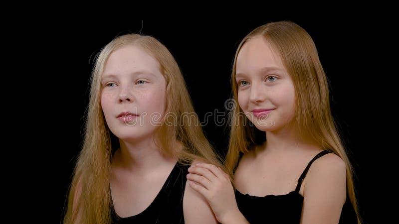 Twee leuke meisjesvrienden die zijwaarts kijken Sluit meisjes van menings omhoog de gelukkige mooie tienermodellen met lang haar stock afbeelding