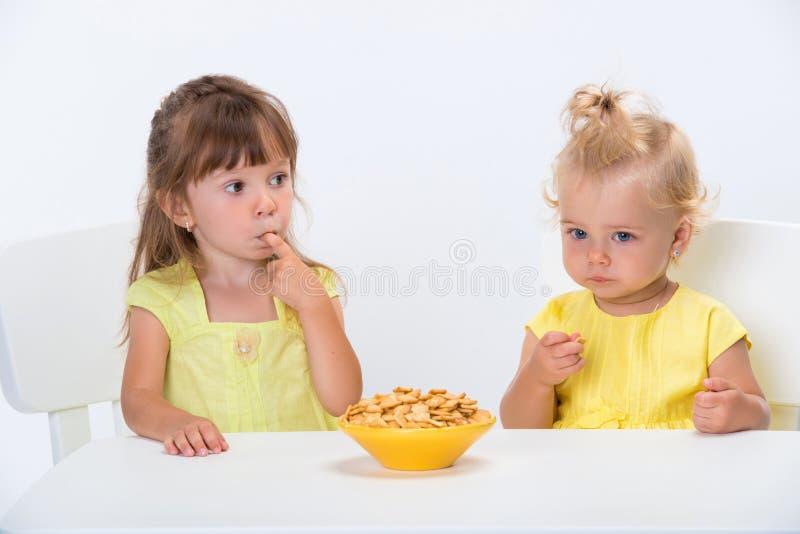 Twee leuke meisjeszusters die in die gele t-shirts graangewas eten schilfert bij de lijst af op witte achtergrond wordt geïsoleer royalty-vrije stock afbeeldingen