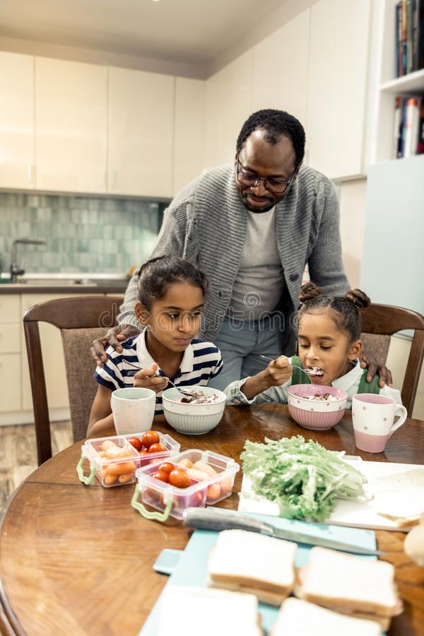 Twee leuke mooie tweelingen die smakelijk ontbijt hebben alvorens naar school te gaan royalty-vrije stock foto