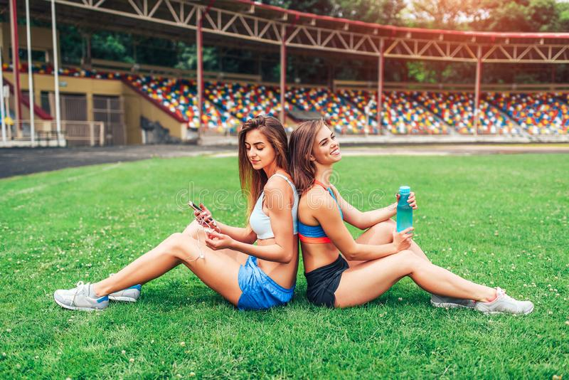 Twee leuke sportieve meisjes die na training ontspannen openlucht royalty-vrije stock afbeelding