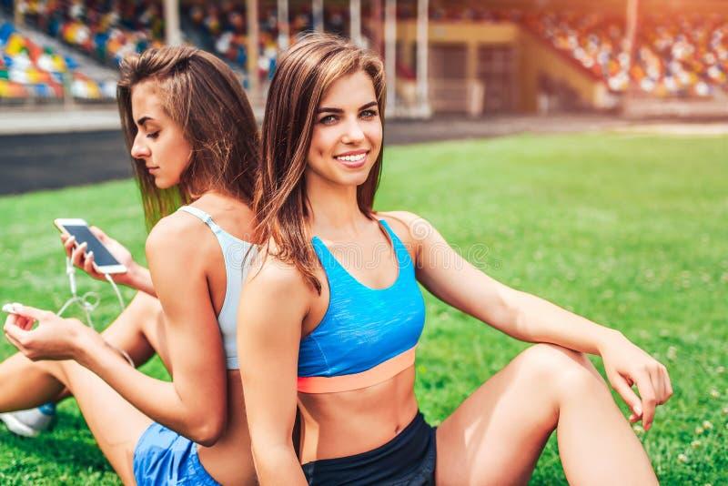 Twee leuke sportieve meisjes die na training ontspannen openlucht royalty-vrije stock foto