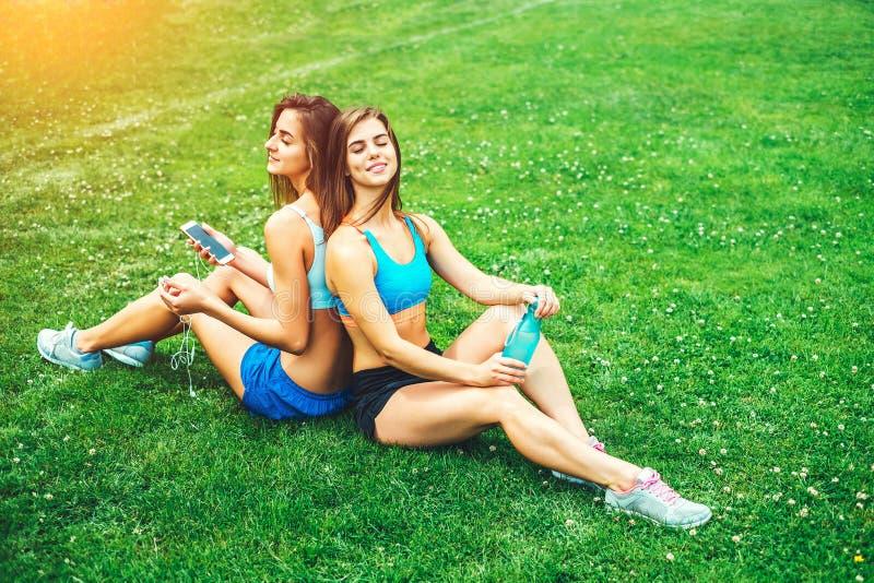 Twee leuke sportieve meisjes die na training ontspannen openlucht stock afbeelding