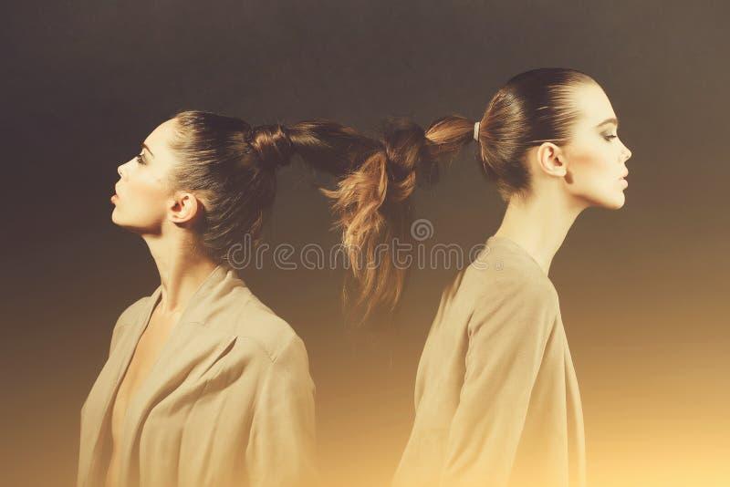 Twee leuke vrouwen met gebonden lang haar in vlecht stock afbeeldingen
