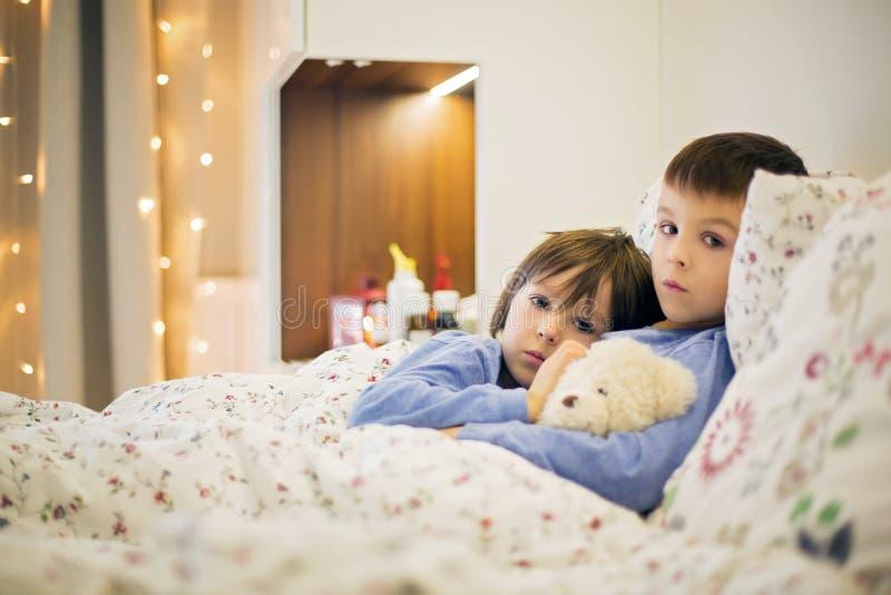 Twee leuke zieke kinderen, jongens, die in bed met koorts blijven royalty-vrije stock foto's