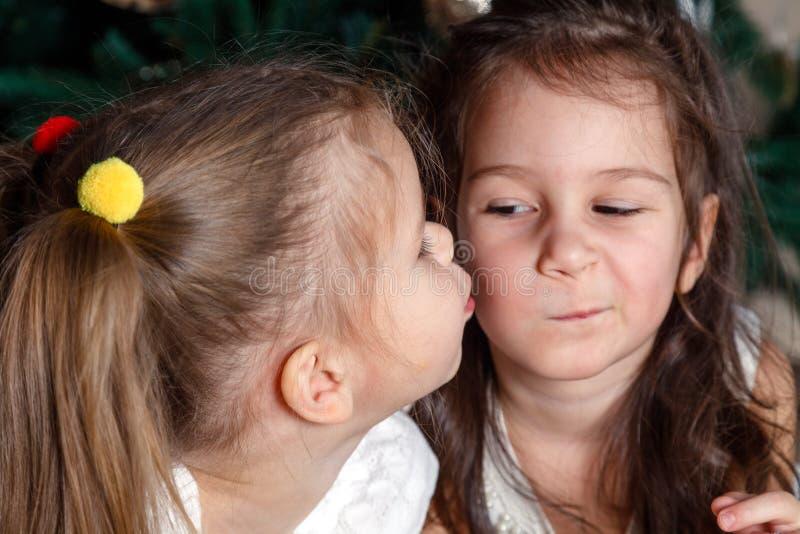 Twee leuke zusters van zelfde leeftijd liggen naast de Nieuwjaarboom E stock fotografie