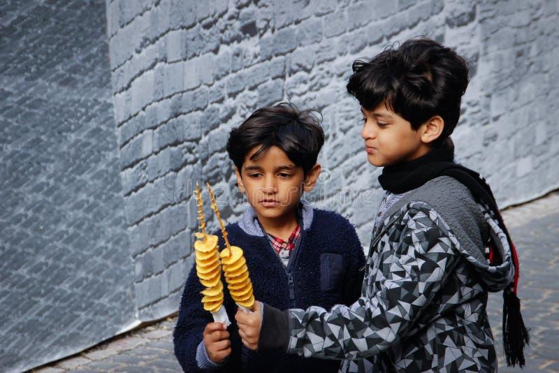 Twee leuke zwart-haired donkere Azerbeidzjaans jongens die, en spaanders op een stok spelen glimlachen eten royalty-vrije stock afbeelding