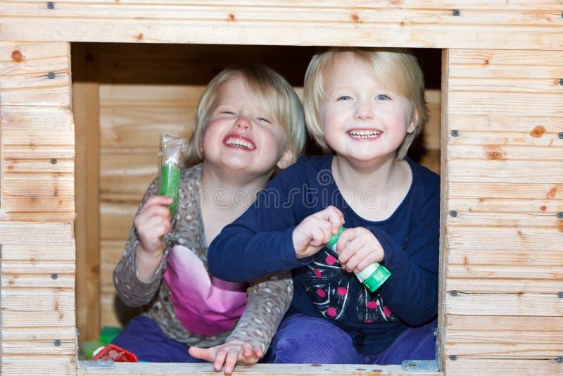 Twee levendige mooie kleine blonde tweelingmeisjes royalty-vrije stock afbeeldingen