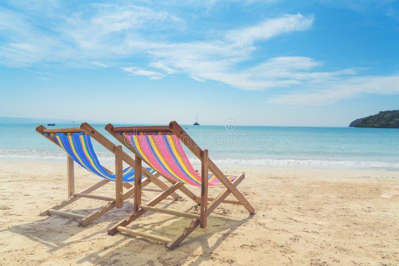 Twee ligstoelen op het witte zand met blauwe hemel en de zomeroverzees stock foto