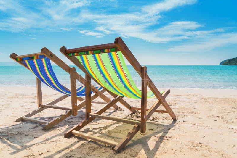 Twee ligstoelen op het witte zand met blauwe hemel en de zomeroverzees royalty-vrije stock foto