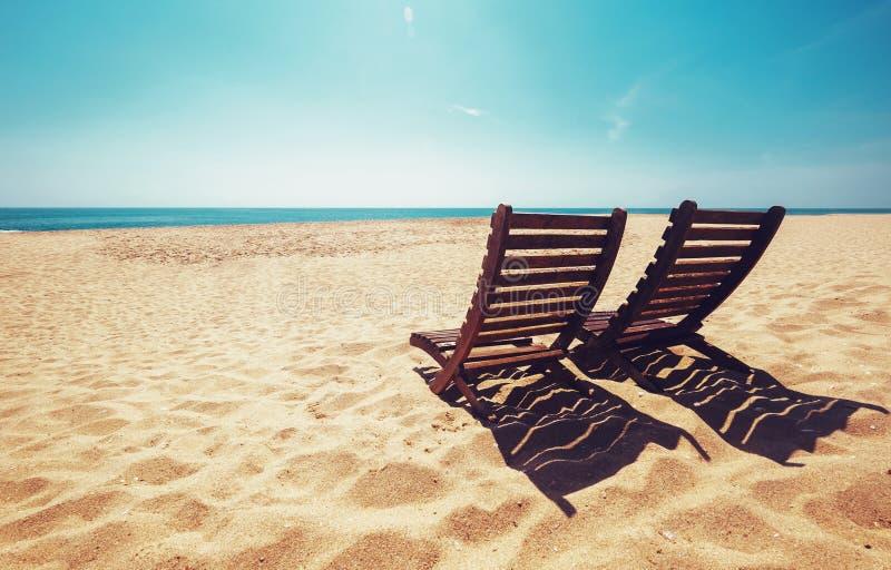Twee ligstoelen op leeg oceaanstrand onder heldere glanzende zon stock foto