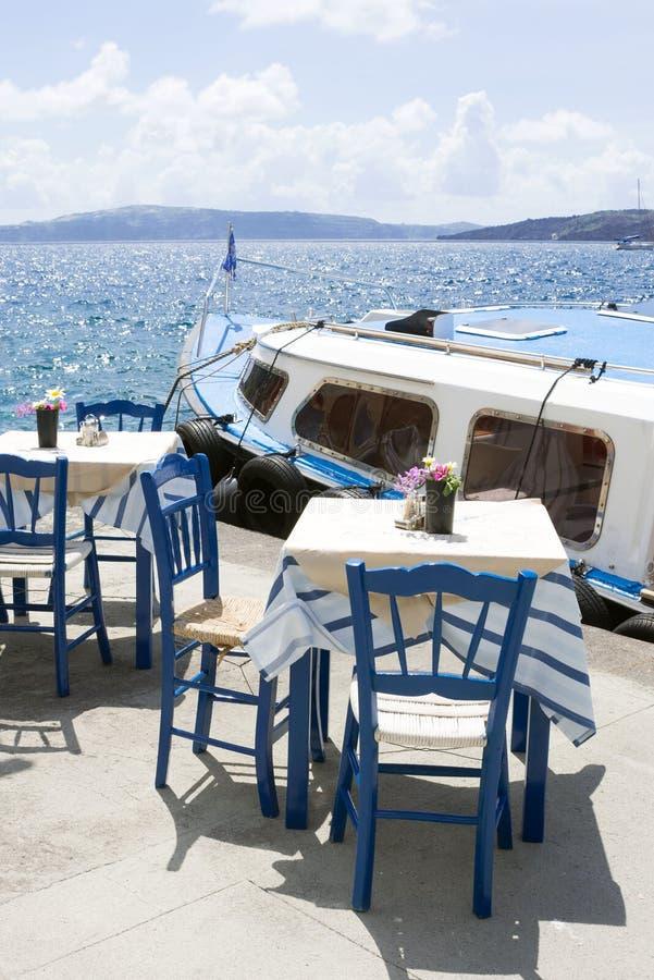 Twee lijsten en stoelen in een comfortabel restaurant op de dijk van de oude haven in de Griekse stad van Fira Heerlijke lunch op stock foto's