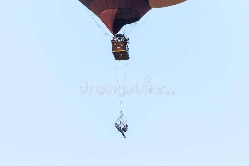 Twee luchtdieacrobaten tonen prestaties op een trapeze van een hete luchtballon bij het festival van de hete luchtballon wordt op stock foto's