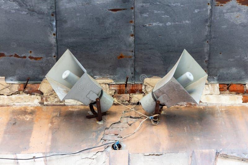 Twee luidsprekers op de muur van een oud gebouw stock fotografie