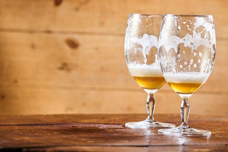 Twee maakten glazen bier op een teller leeg stock fotografie