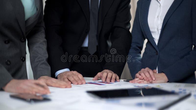 Twee managerdames en mannelijke werkgever die verkoopgrafieken en investeringsplannen vergelijken stock foto
