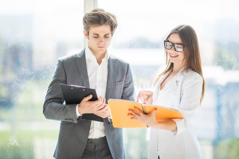 Twee managers die winst bespreken Groep bedrijfsmensen die in bureau samenwerken die over notitieboekje bespreken Jong opstarten royalty-vrije stock afbeelding