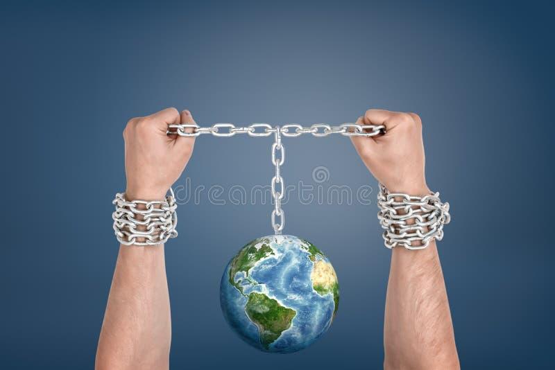 Twee mannelijke handen bonden samen met kettingen en verbonden met een Aardebol tussen hen stock afbeeldingen