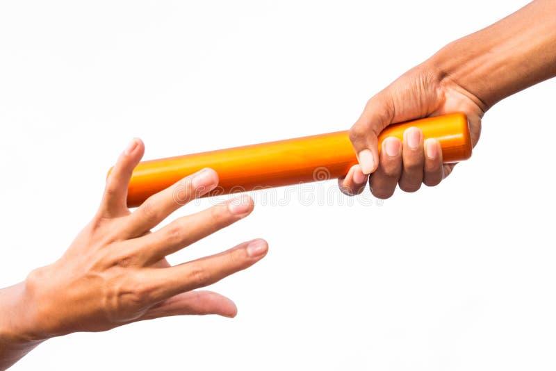 Twee mannelijke handen die een relaisknuppel overgaan stock afbeeldingen