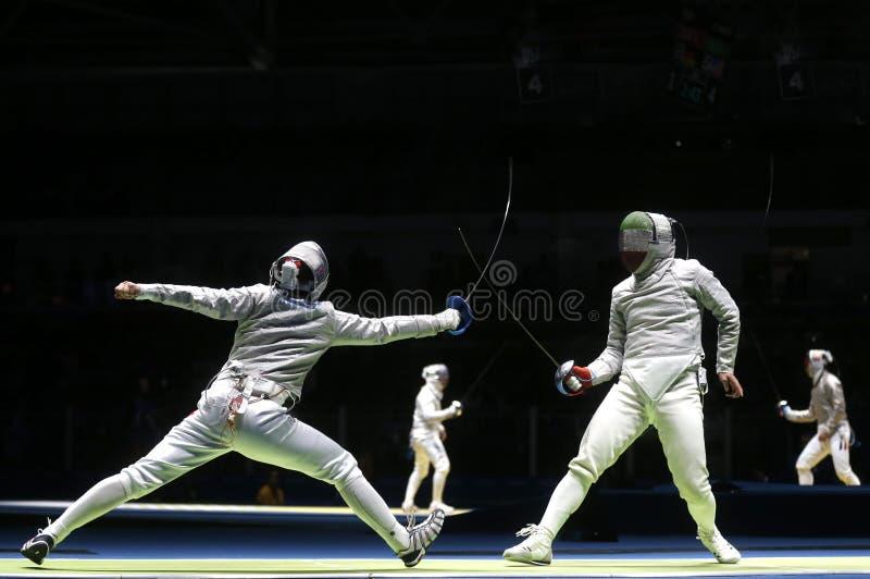 Twee mannelijke het schermen atletenstrijd stock afbeeldingen