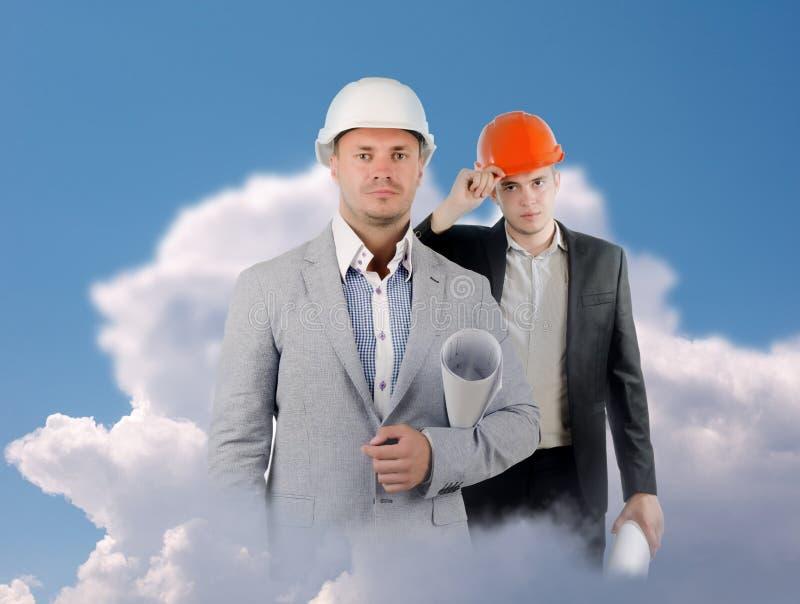 Twee Mannelijke Ingenieurs die op Wolken Camera bekijken stock afbeelding