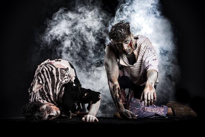 Twee mannelijke zombieën die op hun knieën, op zwarte rokerige achtergrond kruipen stock foto