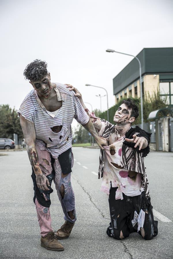 Twee mannelijke zombieën die zich in lege stadsstraat bevinden royalty-vrije stock afbeelding