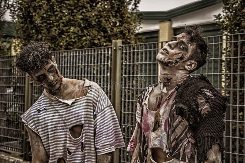 Twee mannelijke zombieën die zich in lege stadsstraat bevinden royalty-vrije stock fotografie