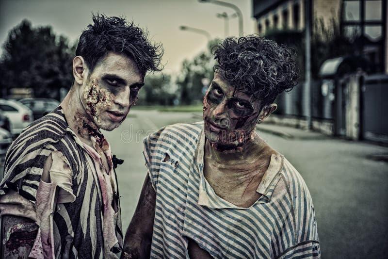 Twee mannelijke zombieën die zich in lege stadsstraat bevinden royalty-vrije stock foto's