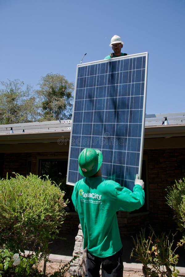 Twee mannelijke zonnearbeiders installeren zonnepanelen royalty-vrije stock afbeelding