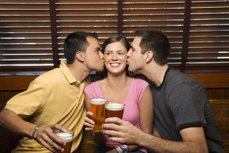 Twee Mannen die Jonge Vrouw kussen stock afbeeldingen