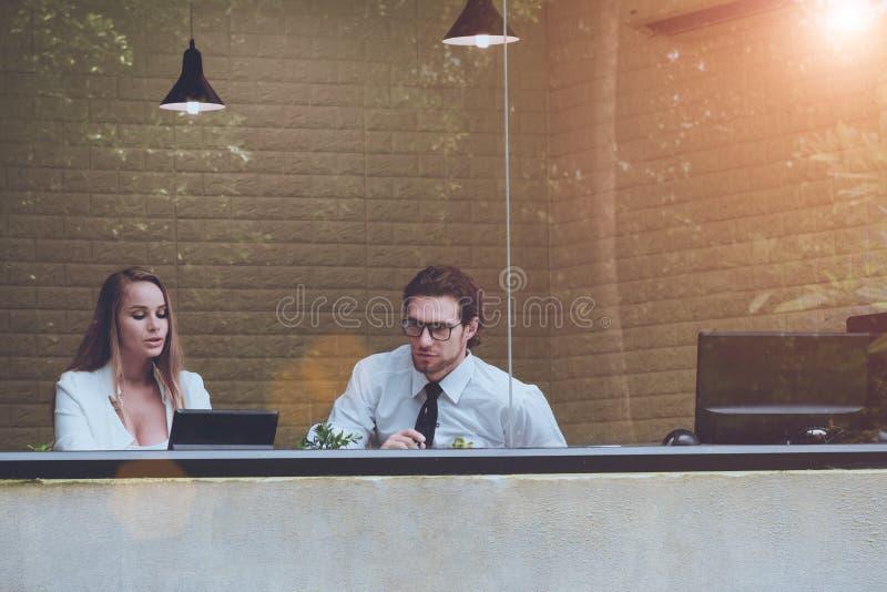 Twee mannen en vrouwen werken in duidelijk bureau met boom en aardbezinning samen aan transparant glas Bedrijfsmensen en royalty-vrije stock fotografie