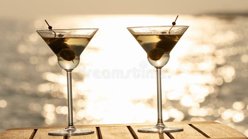 Twee martini-cocktails bij de houten pijler bij zonsondergang Luxeresor royalty-vrije stock afbeeldingen