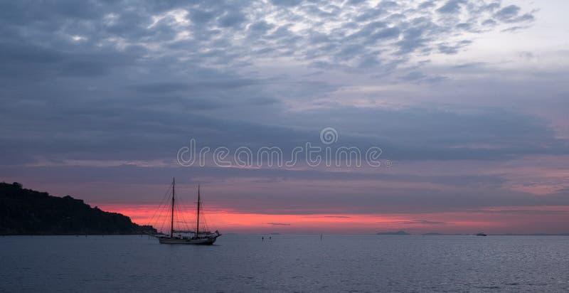 Twee mast varende boot in de verre afstand op de horizon van de kust van Italië in de Baai van Napels dichtbij Sorrento in Italië stock fotografie