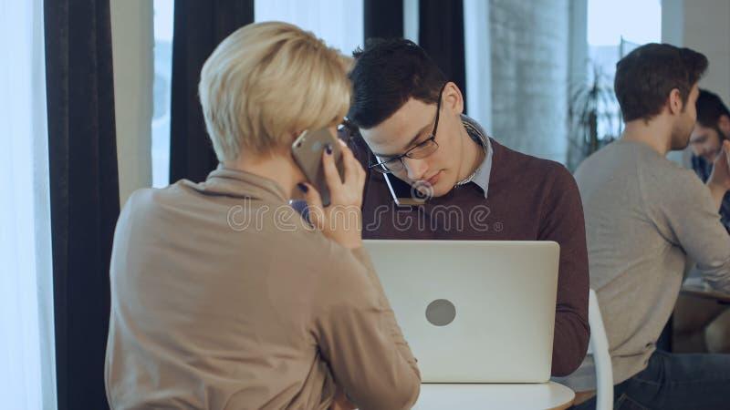 Twee medewerkers die, hebbend telefoongesprekken in de koffie samenwerken stock afbeelding