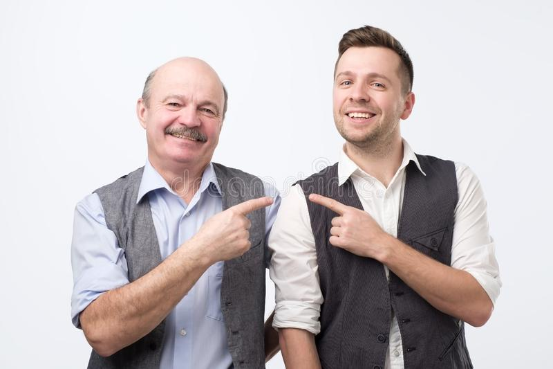 Twee medewerkers die van verschillende leeftijd vinger richten elkaar en camera met gelukkig gezicht bekijken stock fotografie
