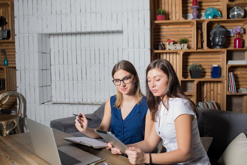Twee medewerkers werken aan de verwezenlijking van nieuwe online opslag gebruikend laptop computer en aanrakingsstootkussen stock foto's