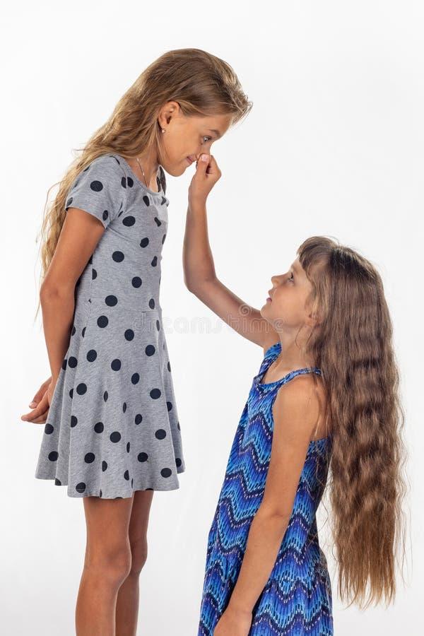 Twee meisjes, één bevonden op een stoel en andere houdt de eerste door de neus stock afbeelding