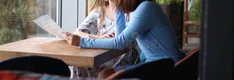 twee meisjes bekijken documenten, het samenkomen klant, contractant stock afbeelding