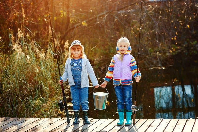Twee meisjes bevinden zich op de brug en houden in hun handenhengels en een emmer voor vissen royalty-vrije stock afbeeldingen