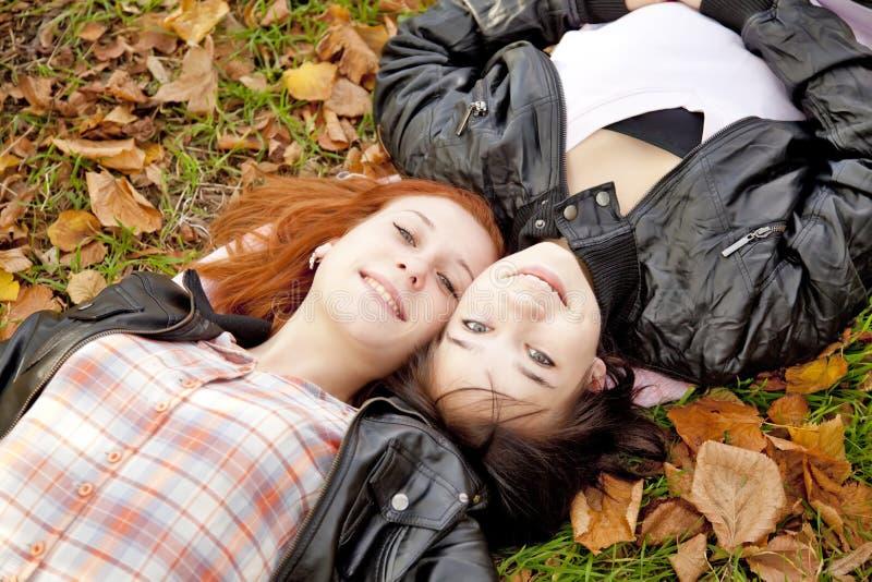 Twee meisjes bij de herfst parkeren. stock afbeeldingen
