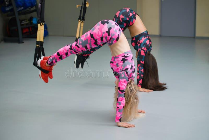 Twee meisjes bij gymnastiek voeren oefeningen met opschortingsriemen die zich op handenbovenkant bevinden uit - neer, selectieve  stock afbeelding