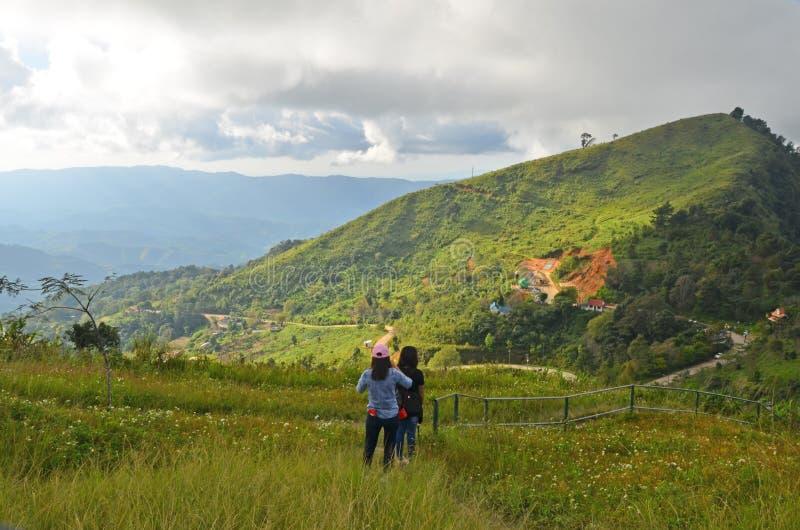 Twee meisjes in de groene weide op bergtop royalty-vrije stock foto's