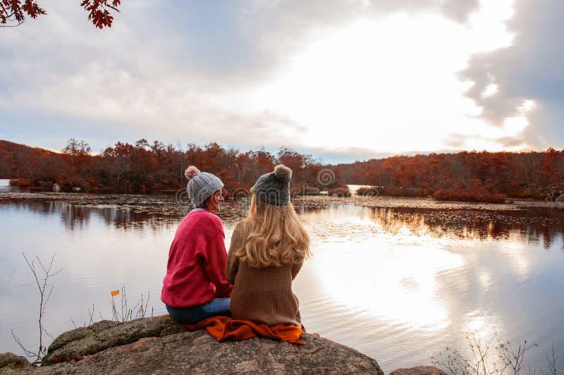 Twee meisjes in de herfst kleedt het bekijken verbazend meer en bos, het concept van de zwerflustreis stock afbeeldingen