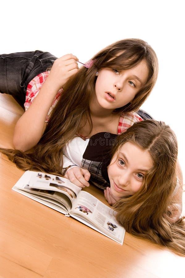 Twee meisjes in de leeftijd van tien die boek lezen stock afbeelding