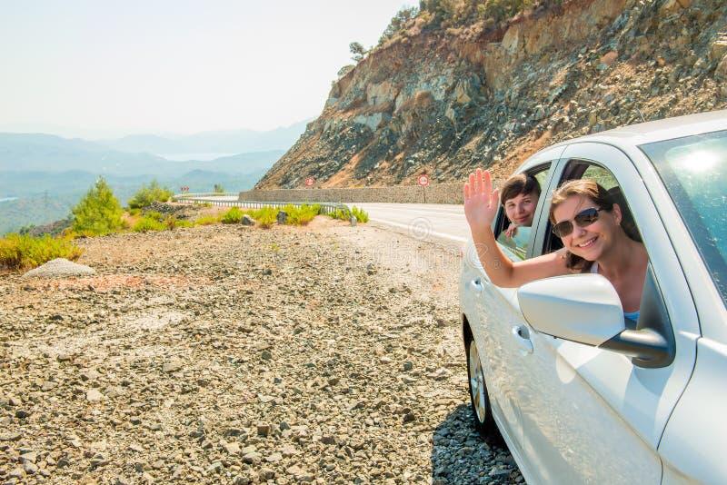 Twee meisjes in de passagierszetel in een auto stock foto
