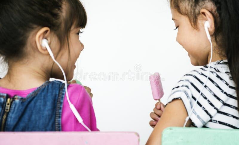 Twee meisjes die aan muziek luisteren royalty-vrije stock afbeeldingen