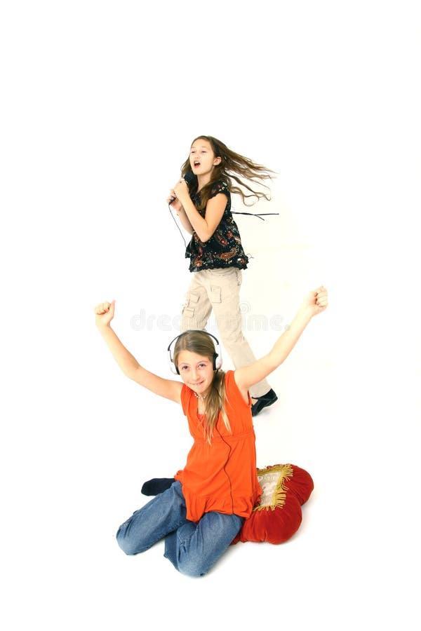 Twee meisjes die aan muziek luisteren stock fotografie
