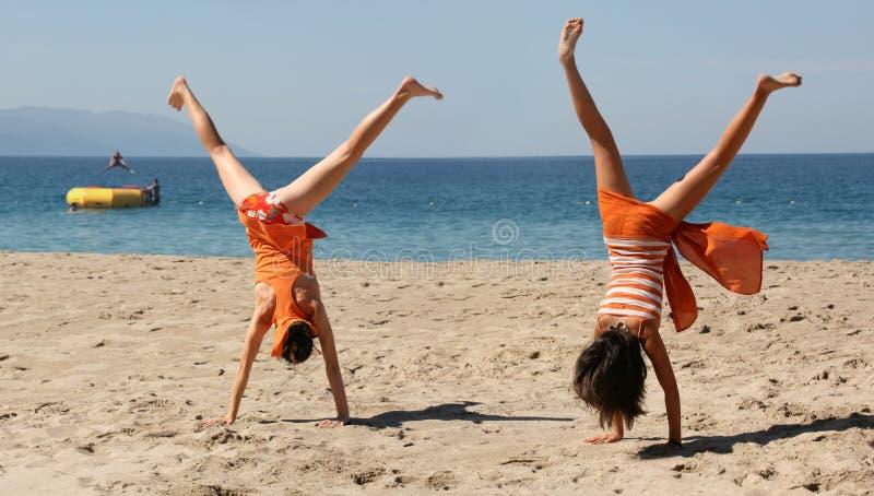 Twee meisjes die cartwheel doen stock afbeeldingen